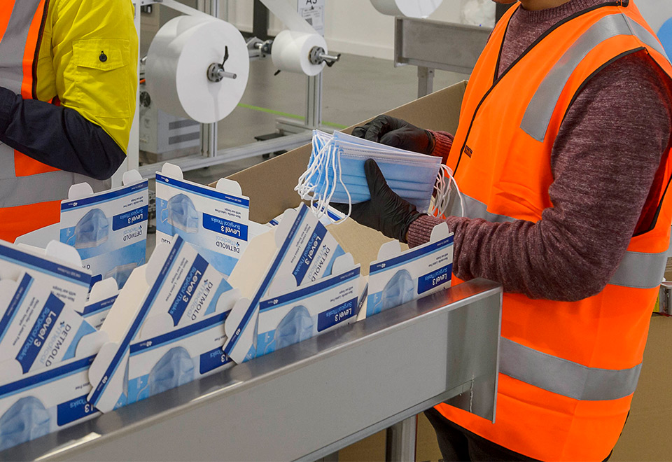Image of masks being packed into cartons