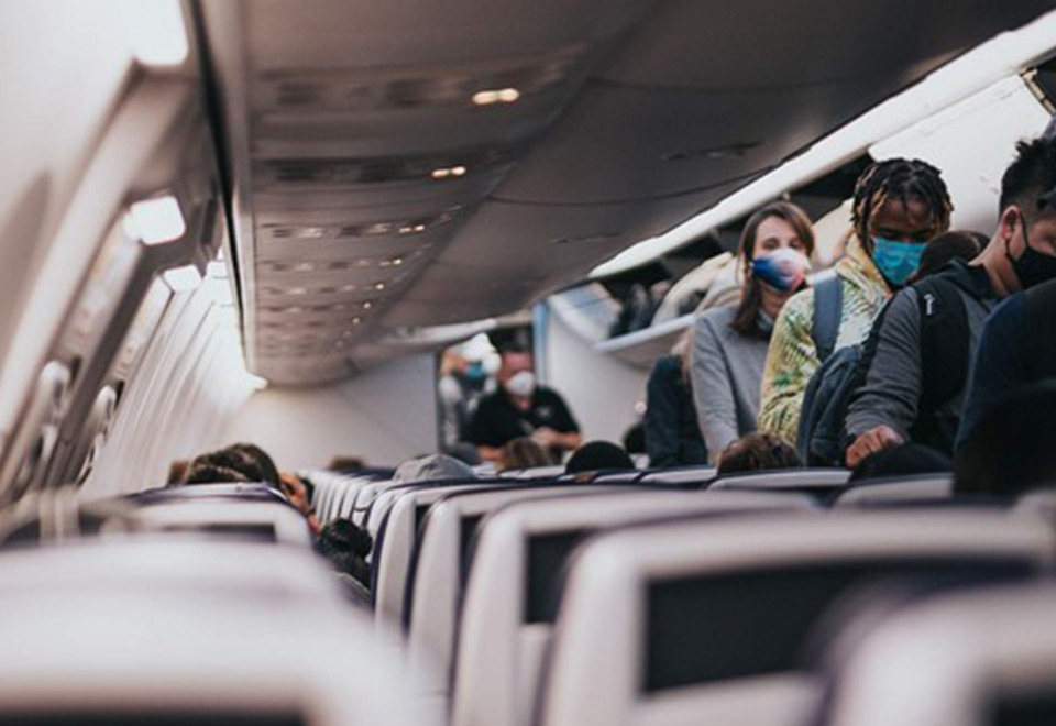 Image of people wearing a mask on an airplane